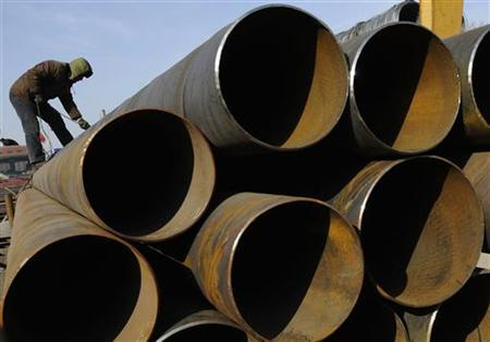 A labourer prepares to transport steel pipes at a steel market in Changzhi, Shanxi province December 31, 2009. REUTERS/Stringer