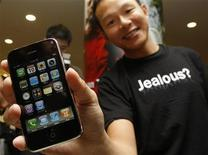 <p>The first buyer of the new 3G iPhone in Hong Kong shows off his phone July 11, 2008. REUTERS/Bobby Yip</p>