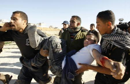 A wounded Palestinians is carried away during a gunbattle near the border between Egypt and the Gaza Strip January 6, 2010. REUTERS/Ahmed Zakot