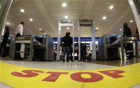 A flight passenger steps into a full-body scanner at the security point of the departure gate at Nice Cote D'Azur International airport in Nice, southeastern France, December 31, 2009. REUTERS/Eric Gaillard