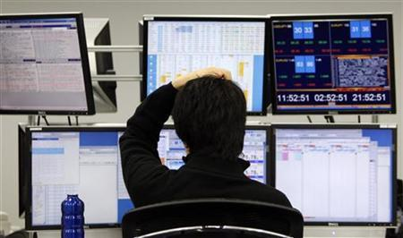 A dealer monitors screens in a dealing room of a brokerage in Tokyo January 4, 2010. REUTERS/Toru Hanai