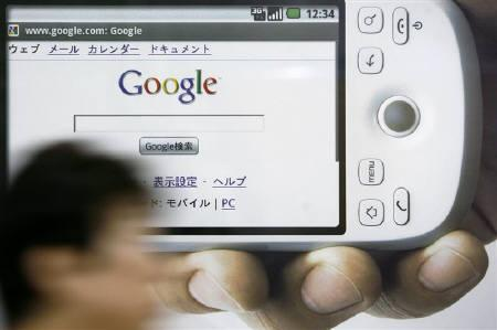 A woman walks past an advertisement of a mobile phone running Google Inc.'s Android operating system at a train station in Tokyo in this July 12, 2009 file photo. REUTERS/Stringer/Files
