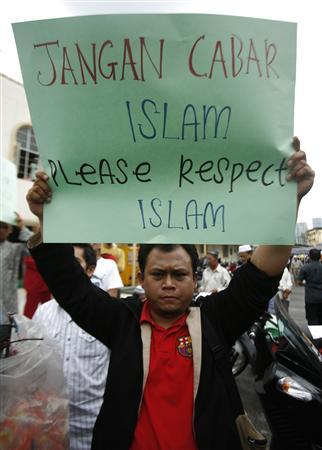 A Muslim demonstrator holds a placard during a protest against a court decision that allows a Catholic newspaper to use the word ''Allah'' to describe the Christian God in its Malay language editions, after Friday prayers outside a mosque in Kuala Lumpur January 8, 2010. The placard says ''Don't Challenge Islam, Please Respect Islam.'' REUTERS/Bazuki Muhammad