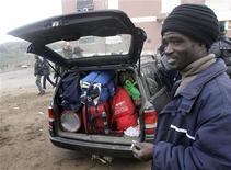 <p>Degli immigrati lasciano Rosarno in auto. REUTERS/Antonino Condorelli</p>