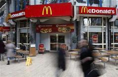 <p>Passanti passeggiano davanti a un McDonald's. REUTERS/Radu Sigheti</p>