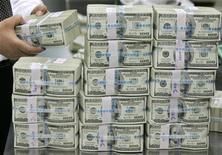 <p>Сотрудник банка складывает пачки 100-долларовых купюр в хранилище в Сеуле 26 февраля 2009 года. США безвозмездно предоставят Молдавии финансовую помощь в размере $262 миллионов на реконструкцию дорог и ирригацию, сказал Рейтер советник премьер-министра Игорь Волницкий. REUTERS/Lee Jae-Won</p>