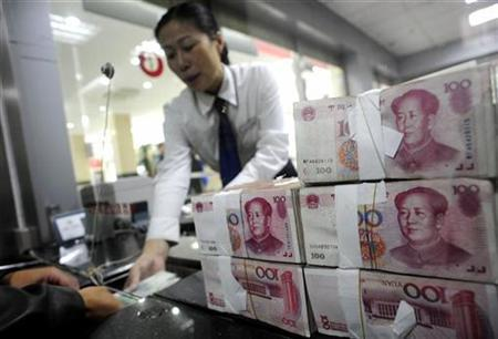 An employee hands Renminbi banknotes to a customer at a branch of the Industry and Commercial Bank of China in Hefei, Anhui province, October 9, 2008. REUTERS/Stringer