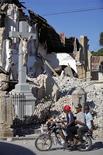 <p>Residentes pasan cerca de edificios colapsados en Puerto Príncipe, 13 ene 2010. Chile comprometió el envío de un avión con ayuda para las víctimas del terremoto que afectó el martes a Haití y el traslado de un delegado especial con el fin de apoyar a la nación caribeña. Haití teme que miles de personas hayan muerto como consecuencia del poderoso sismo, el peor en 200 años, que demolió escuelas, hospitales, barrios humildes y hasta el palacio presidencial. REUTERS/Eduardo Munoz</p>
