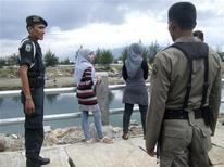 <p>Sharia police reprimand two women for wearing tight trousers in Banda Aceh, December 18, 2009. REUTERS/Masako Iijima</p>