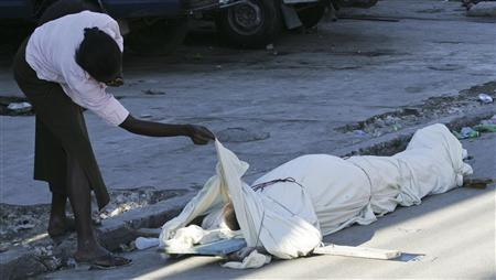 A woman checks a body after an earthquake in Port-au-Prince January 14, 2010. REUTERS/Kena Betancur