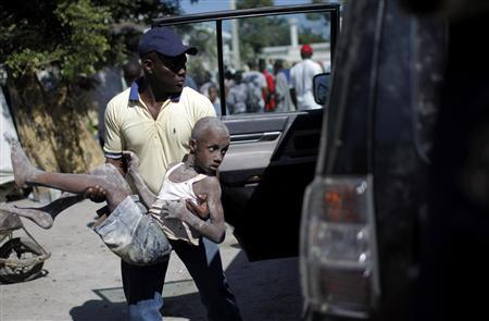 A resident carries Samael Jachond, who was rescued from the remains of his house, four days after a major earthquake hit the capital Port-au-Prince January 15, 2010. REUTERS/Carlos Barria