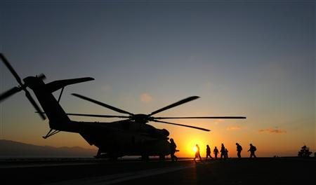 U.S. Navy helicopters are prepped for takeoff in the early morning sunrise onboard the USS Carl Vinson as relief efforts continue off the shore of Port-au-Prince January 17, 2010. REUTERS/Hans Deryk