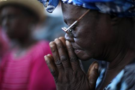 A Haitian woman prays as she attends an open air Catholic mass next to the ruins of a cathedral in Port-au-Prince January 17, 2010. REUTERS/Jorge Silva