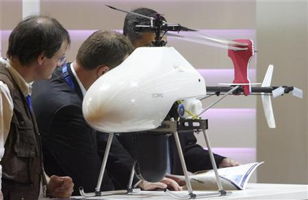 Visitors examine a Scorpio drone, a light VTOL mini UAV system for multipurpose missions made by EADS, at the ''MILIPOL'' International State Security Exhibition in Paris, October 9, 2007. REUTERS/Regis Duvignau