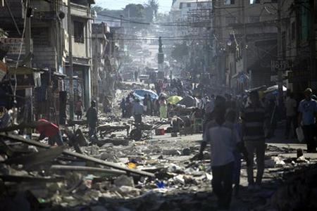 People walk on the damaged streets of Port-au-Prince, January 16, 2010. EUTERS/Carlos Barria