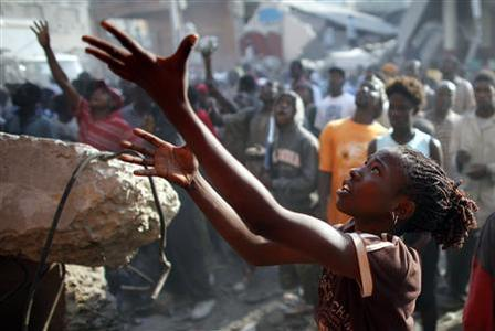 A girl reaches out for goods thrown by looters from a destroyed store in downtown Port-au-Prince, January 18, 2010. REUTERS/Jorge Silva