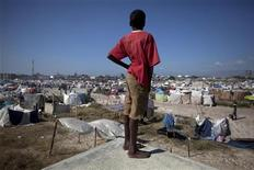 <p>Un bambino osserva uno degli accampamenti di Port-au-Prince, ad Haiti. REUTERS/Carlos Garcia Rawlins</p>