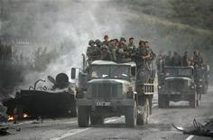 <p>Грузинские солдаты проезжают взорванный грузинский бронетранспортер недалеко от города Гори 11 августа 2008 года. Грузия не намерена увеличивать расходы на военные цели в 2010 году и рассчитывает привлечь в ближайшие два года около $3 миллиардов от приватизации, сообщил Рейтер министр финансов Каха Баиндурашвили. REUTERS/David Mdzinarishvili/Files</p>