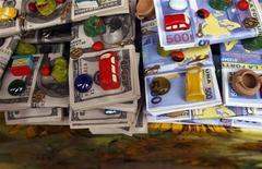 <p>Образцы долларовых банкнот и счастливых талисманов на рынке в Лиме. 30 декабря 2009 года. Экономические свободы в мире были резко ограничены в прошлом году в результате масштабных госрасходов на борьбу с кризисом, и эта тенденция может поставить под угрозу перспективы развития мировой экономики. REUTERS/Pilar Olivares</p>