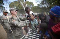 <p>Американский солдат держит на руках девочку во время распределения продуктов питания в Порт-о-Пренсе 19 января 2010 года. Угроза беспорядков и грабежей, спровоцированных потрясшим Гаити землетрясением, ослабевает после того, как на остров прибыли американские военнослужащие, которым удалось немного успокоить тысячи оставшихся без жилья, голодных и отчаявшихся гаитян. REUTERS/Jorge Silva</p>