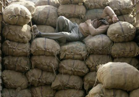 A man sleeps on the sacks filled with potatoes inside a lorry at a wholesale market in New Delhi in this December 18, 2009 file photo. Annual food prices eased in early January for the third week running, government data showed on Thursday. REUTERS/Rupak De Chowdhuri/Files