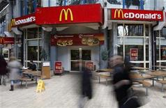 <p>People walk in front of a McDonald's restaurant in Bucharest January 7, 2010. REUTERS/Radu Sigheti</p>