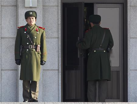 A North Korean soldier stands guards as a fellow soldier walks into the building on the north side of the truce village of Panmunjom in the demilitarised zone separating the two Koreas in Paju, about 55 km (34 miles) north of Seoul, January 21, 2010. REUTERS/Jo Yong-Hak