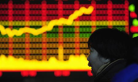 A woman looks at an electronic board with stocks information at a brokerage house in Hefei, Anhui province January 12, 2010. REUTERS/Stringer