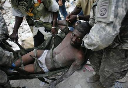 Rico Dibrivell, 35, is attended by a U.S. military rescue team after being freed from the rubble of a building in Port-au-Prince January 26, 2010. REUTERS/Eduardo Munoz