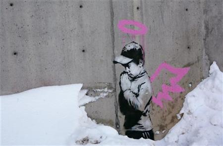 Artwork by the artist Banksy is shown on a wall during the Sundance Film Festival in Park City, Utah January 22, 2010. REUTERS/Robert Galbraith