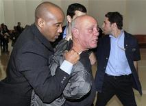 <p>Представитель службы безопасности задержал мужчину, который бросил ботинком в голову председателя Верховного суда Израиля. 27 января 2010 года. Неизвестный мужчина в среду бросил ботинком в голову председателю Верховного суда Израиля Дорит Бейниш, сообщили очевидцы происшествия. REUTERS/Ouria Tadmor</p>
