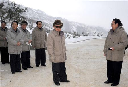 North Korean leader Kim Jong-il (C) poses for photos on a road as he goes around to give field guidance about highways in North Pyongan Province, northwest of Pyongyang in this picture released by the North's KCNA news agency January 28, 2010. REUTERS/KCNA