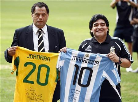 Argentina soccer coach Diego Maradona (R) poses with Danny Jordaan, chairman of the 2010 Local Organising Committee (LOC), before exchanging soccer jerseys at Soccer City, also known as the FNB Stadium in Johannesburg, January 21, 2010. REUTERS/Siphiwe Sibeko