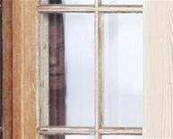 <p>Foto de archivo del director de cine Roman Polanski en una ventana de su casa de descanso en Gstaad, Suiza, dic 5 2009. Polanski, quien se encuentra bajo arresto domiciliario en Suiza, no acudirá el próximo mes al Festival de Cine de Berlín, pese a que la última película del director será presentada, dijo el viernes el director del evento, Dieter Kosslick. REUTERS/Christian Hartmann</p>