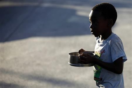 A boy walks past after receiving food from a Haitian foundation in downtown Port-au-Prince January 29, 2010. REUTERS/Jorge Silva