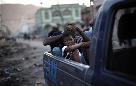 A young looter who was arrested, sits in the back of a police truck in a commercial area of Port-au-Prince January 30, 2010. REUTERS/Carlos Barria