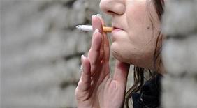 <p>Женщина курит сигарету рядом с офисным зданием в центре Лондона 9 мая 2009 года. Правительство Великобритании обещает новую антитабачную кампанию и планирует запретить курение на улице - у входов в здания, а также при детях - в домах, квартирах и машинах. REUTERS/Toby Melville</p>