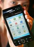 """<p>Foto arquivo mostra funcionária da Willcom Inc. apresentando o smart phone """"W-ZERO3"""" da Sharp Corp em Tóquio. A expansão na demanda por celulares inteligentes novos e mais baratos ajudou a recuperação do mercado de celulares no final do ano passado. 20/10/2005</p>"""