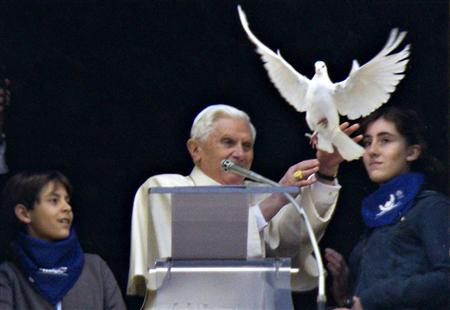 Pope Benedict XVI, flanked by two children, releases a dove at the end of his Angelus prayer at the Vatican January 31, 2010. REUTERS/Max Rossi