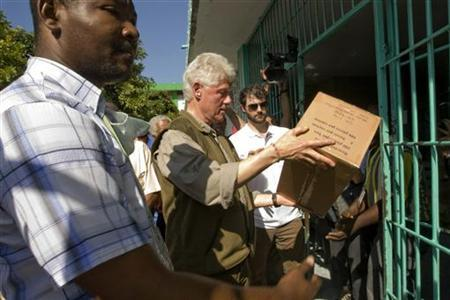 Former U.S. President Bill Clinton (C), the U.N. Special Envoy to Haiti, helps load supplies at the General Hospital in Port-au-Prince January 18, 2010. REUTERS/UN/Logan Abassi
