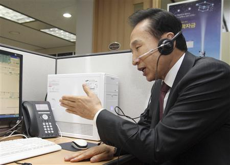 South Korean President Lee Myung-bak talks with a student over a phone at a call centre for student loan at the Korea Student Aid Foundation in Seoul February 2, 2010. North and South Korea have been secretly trying to set up a summit by mid-year, news reports said on Tuesday, but the South insisted the destitute North would not be offered any payment to entice it to a meeting. Lee has said he wants a firm commitment from Pyongyang to rejoin disarmament talks and to scrap its nuclear arms programme before agreeing to what would be only the third summit between the states still technically at war. REUTERS/Jo Bo-hee/Yonhap