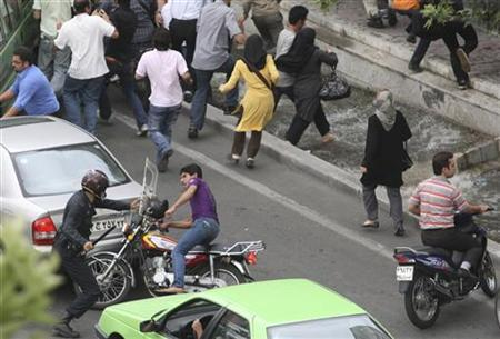 Riot police hits a motorcyclist with a baton during a protest against the election results in Tehran June 14, 2009. REUTERS/Stringer