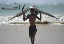 <p>Сомалийский рыбак несет на голове рыбу-меч в портовом городе Кисмайо 6 сентября 2007 года. Трехдневная задержка в отгрузке нефти на терминале французской компании Total в Анголе была вызвана пробоиной в трубопроводе, в которой винят рыбу-меч, сообщают трейдеры. REUTERS/Stringer</p>