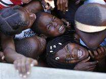 <p>Дети, зажатые толпой, в ходе распределения продовольствия в городе Порт-о-Пренс. 28 января 2010 года. Власти Гаити в понедельник допросили американских миссионеров, которые обвиняются в попытке нелегального вывоза детей из страны. REUTERS/Eduardo Munoz</p>
