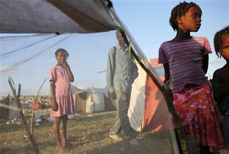 Earthquake survivors stand next to a makeshift tent at the Cite Soleil in Port-au-Prince February 2, 2010. REUTERS/Eliana Aponte