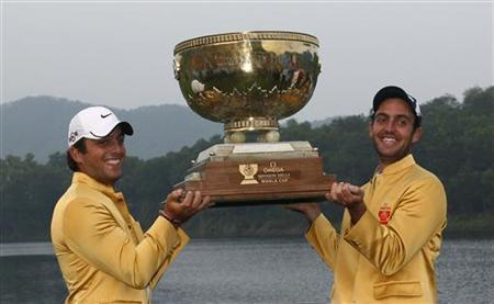 Edoardo Molinari (R) of Italy and teammate Francesco Molinari hold aloft the trophy after winning the World Cup golf tournament in Dongguan November 29, 2009 file photo. REUTERS/Bobby Yip