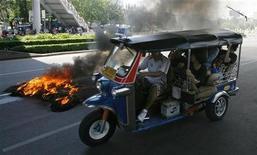 <p>Таиландское мото-такси тук-тук проезжает мимо горящих шин в Бангкоке 13 апреля 2009 года. В Таиланде действует целая сеть мото-такси, водители которых проносятся на огромных скоростях мимо бесконечного потока машин, игнорируя правила дорожного движения. Часто можно заметить медленно плетущиеся тук-туки, которые везут пострадавших пассажиров в ближайшую больницу. Чтобы хоть как-то обезопасить себя, выбирайте водителей в оранжевых жилетах - у них хотя бы есть лицензия и запасной шлем. REUTERS/Chaiwat Subprasom</p>