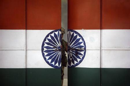 An Indian Border Security Force (BSF) soldier opens a gate at the border with Pakistan in Suchetgarh, southwest of Jammu, in this January 12, 2010 file photo. REUTERS/Mukesh Gupta/Files