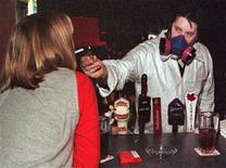 """<p>Бармен в противогазе прикуривает сигарету клиенту в одном из заведений Ванкувера 1 января 2000 года. Планы Ванкувера провести Олимпиаду без курения были разрушены, когда Международный олимпийский комитет (МОК) попросил городские власти создать специальные места для любителей """"подымить"""" REUTERS/Lyle Stafford</p>"""