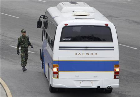 A border security soldier of South Korea checks a bus carrying a South Korean delegation at the CIQ (customs, immigration and quarantine) office, just south of the demilitarized zone separating the two Koreas, in Paju, north of Seoul February 8, 2010. REUTERS/Lee Jae-Won